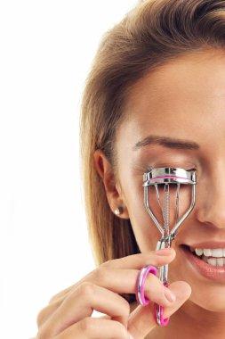woman using eyelash curler