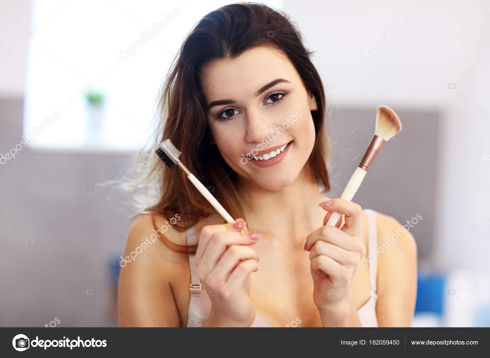Giovane donna attraente che fa trucco mentre si guarda allo specchio in bagno foto stock - 94 si fa in bagno ...