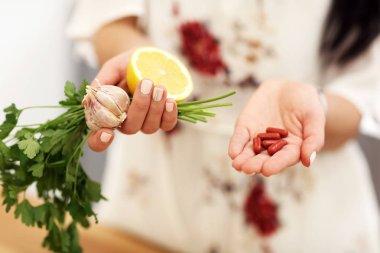 Young woman holding medicine and lemon garlic parsley