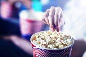 Männliche Hand holt Popcorn aus der Box im Kino