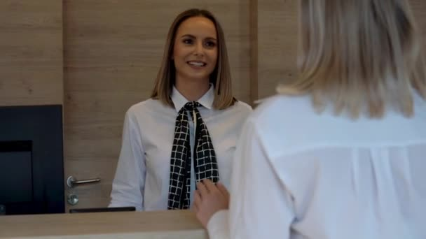 Rezeptionistin hilft Hotelgast am Schreibtisch