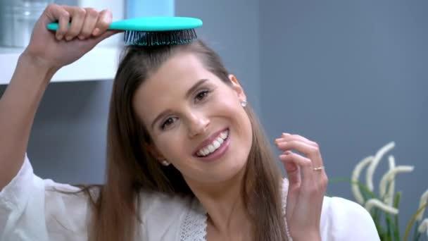Glücklich selbstbewusste erwachsene Frau beim Haareputzen im Badezimmer am Morgen