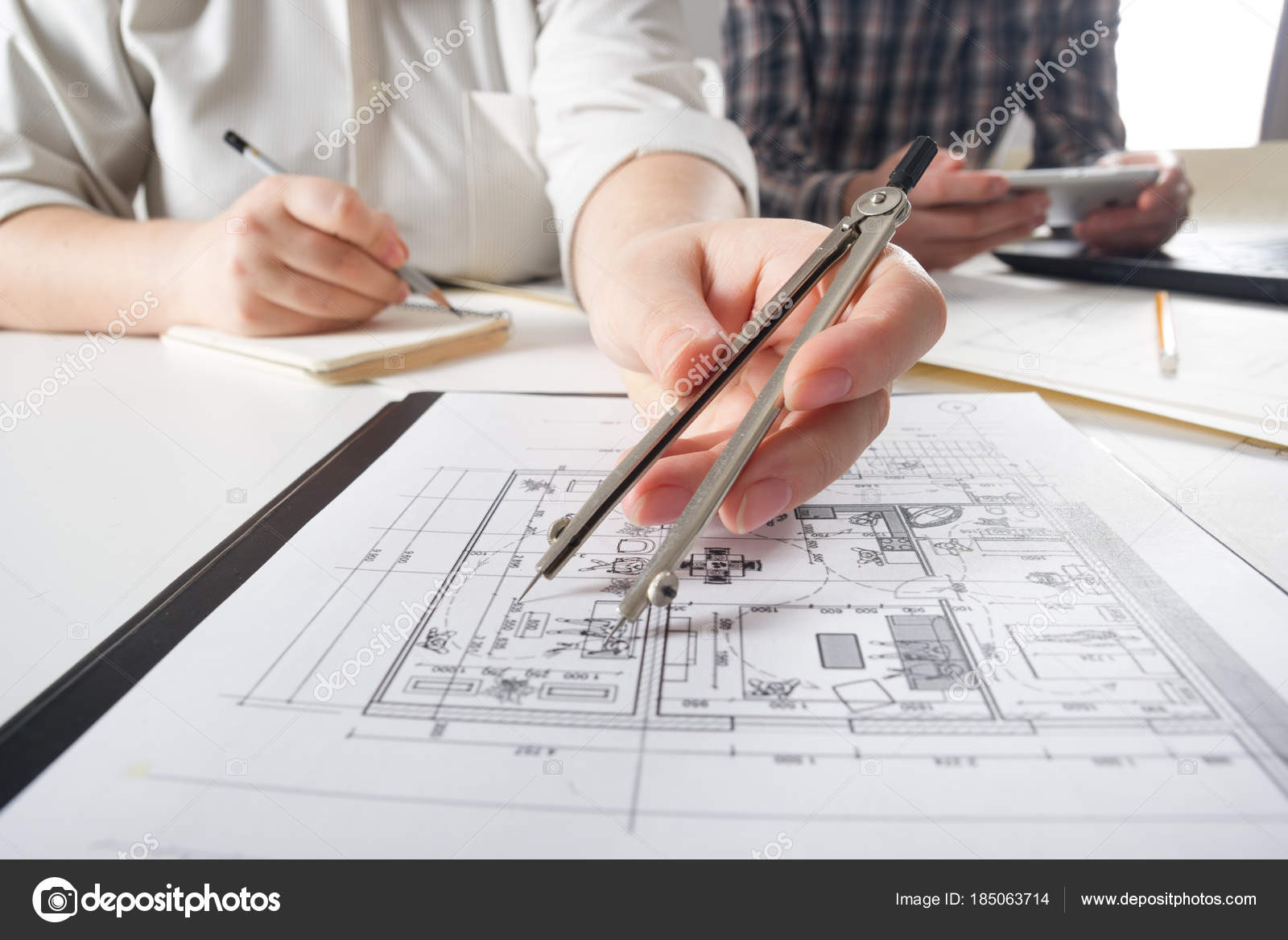 Architects working on blueprint real estate project architect architects working on blueprint real estate project architect workplace architectural project blueprints malvernweather Gallery