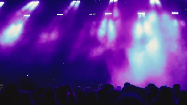 A koncerttömeg és a színpadi fények sziluettje.Koncert és élő zene