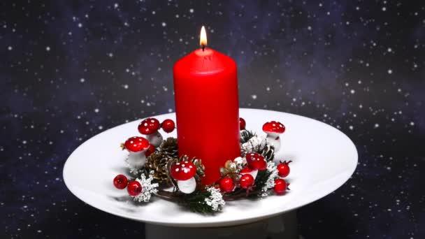 Weihnachtsdekoration mit Adventskranz und brennender Kerze auf Drehtisch