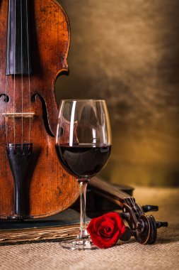 Red wine in glass and old violin