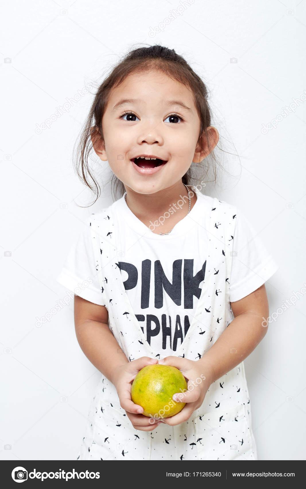 Retrato hermoso de niño feliz pelo largo pelo asiático y negro niña.  Gestos. mano tiene la naranja — Foto de pongans68@gmail.com| ...