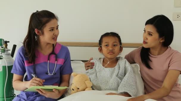 Lékař konzultuje Frankovi a jeho matka, roztomilá malá dívka spí na posteli v dětské nemocnici