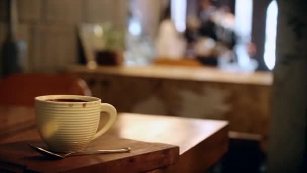 A pultnál lévő kávézó kávét rendel a háttérben.