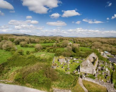 Aerial view of a beautiful old ruins of an Irish church and burial graveyard in county clare, Ireland. Set in the burren national park countryside landscape.