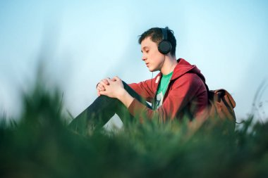 Teenager on green lawn listening music