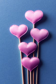 Pink hearts on wooden sticks on blue backdrop closeup