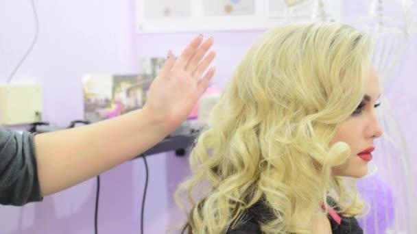 Profesionální vlasy kadeře pro model dívka v salonu krásy nebo ve studiu