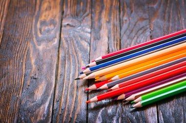 Color pencils on wooden table, school supplies stock vector