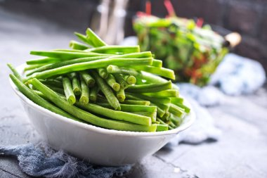 green beans in bowl and fresh leaves of mangold on table