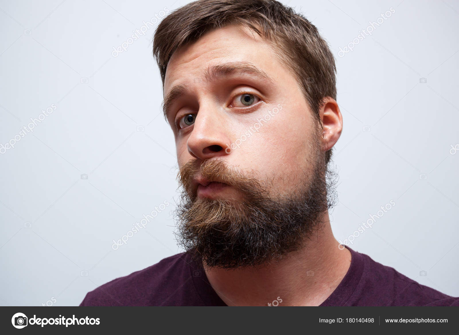 young bearded man looking at his messy long beard and moustache in