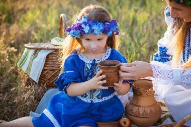 Cute little girl in blue floral wreath drinking fresh milk from clay mug