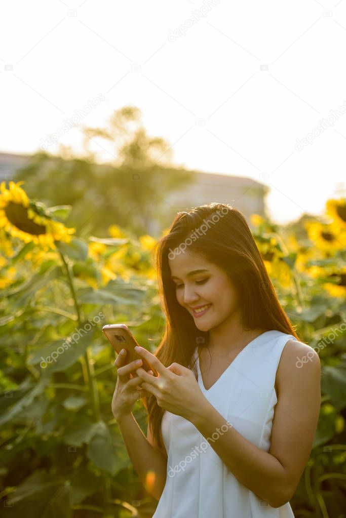 Young happy Asian woman smiling while using mobile phone in the