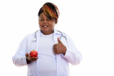 Studio shot of happy fat black African woman doctor smiling whil
