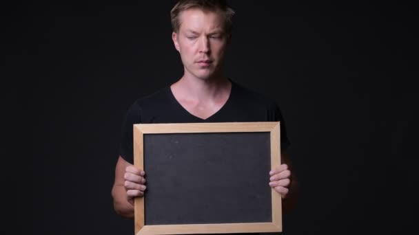 Young handsome man holding blackboard against black background