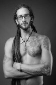 junger hübscher hispanischer Mann mit Dreadlocks ohne Hemd in schwarz und weiß