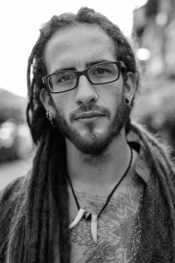 Young handsome Hispanic tourist man with dreadlocks outdoors in black and white