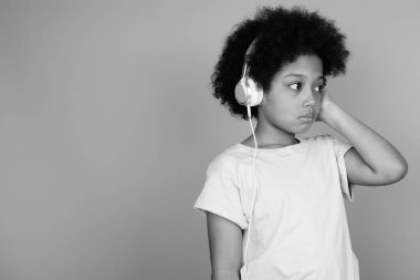 Young cute African girl with Afro hair listening to music in black and white