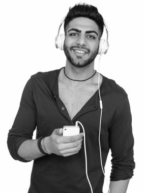 Studio shot of young happy Indian man listening to music while holding mobile phone isolated against white background