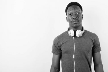 Young handsome African man wearing headphones against white background