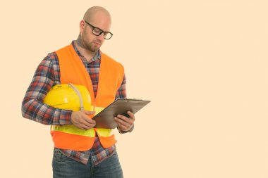 Bald muscular man construction worker holding safety helmet and reading on clipboard