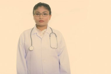 Studio shot of young fat Persian woman doctor with eyeglasses isolated against white background