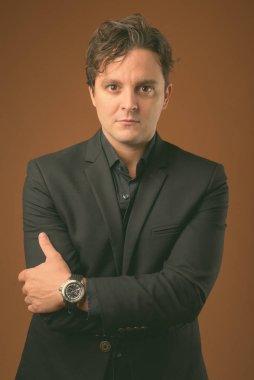 Studio shot of Italian businessman against brown background