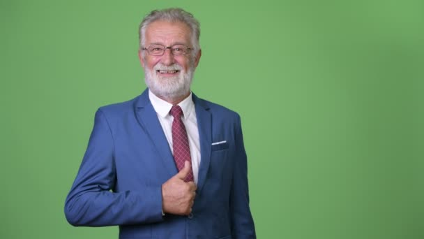Handsome senior bearded businessman against green background