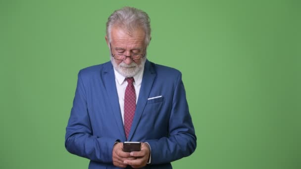 Handsome senior bearded businessman against green background