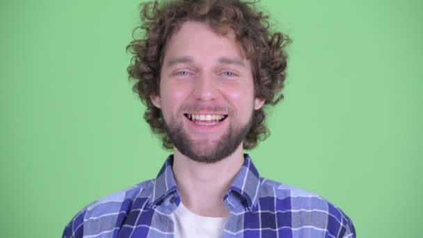 Face of happy young bearded hipster man smiling