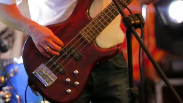 Člověk hraje kytaru na koncertě. Detail
