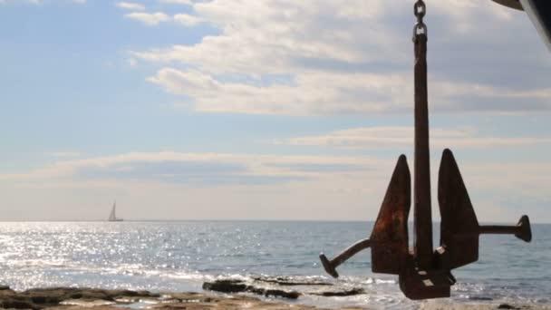 Plachetnice se plaví na pozadí velké kotvy