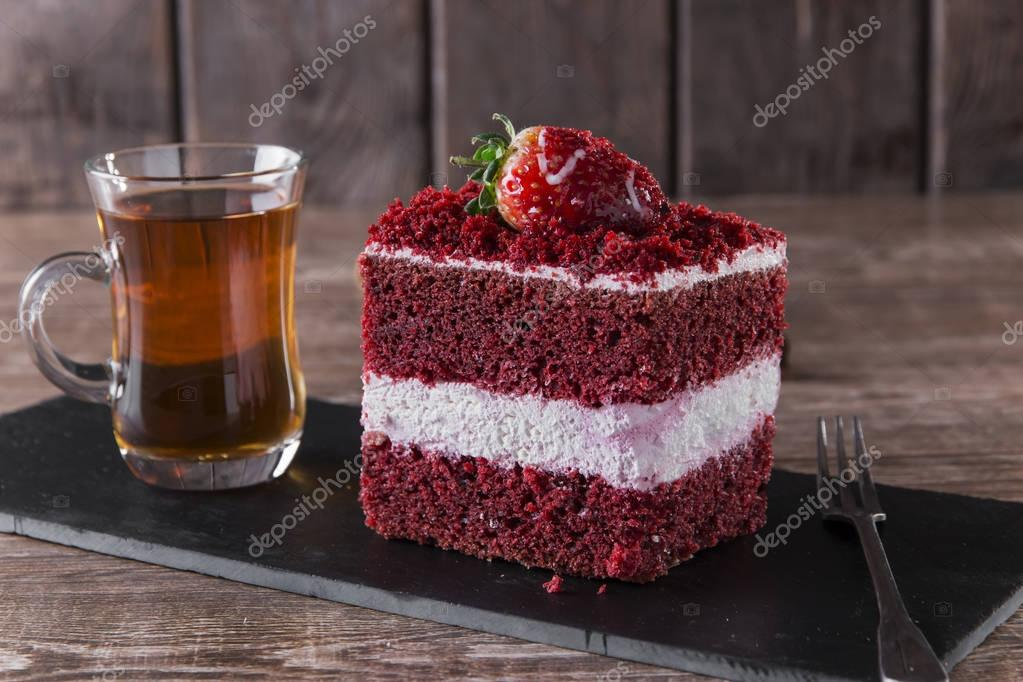 Slice Of Red Velvet Cake With White Frosting Is Garnished With