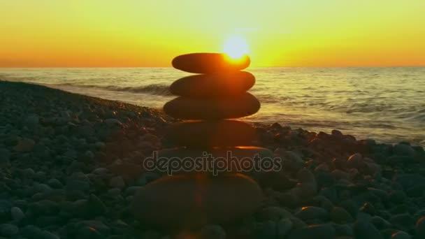 pyramidové kameny v pozadí moře slunce ženské ruce klade malý kámen na vrcholu pyramidy kameny