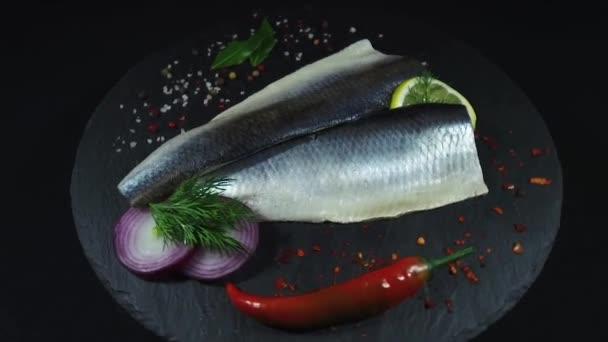 Fischfilet Hering und Gewürze schwarzer Hintergrund, 360-Grad-Drehung von oben