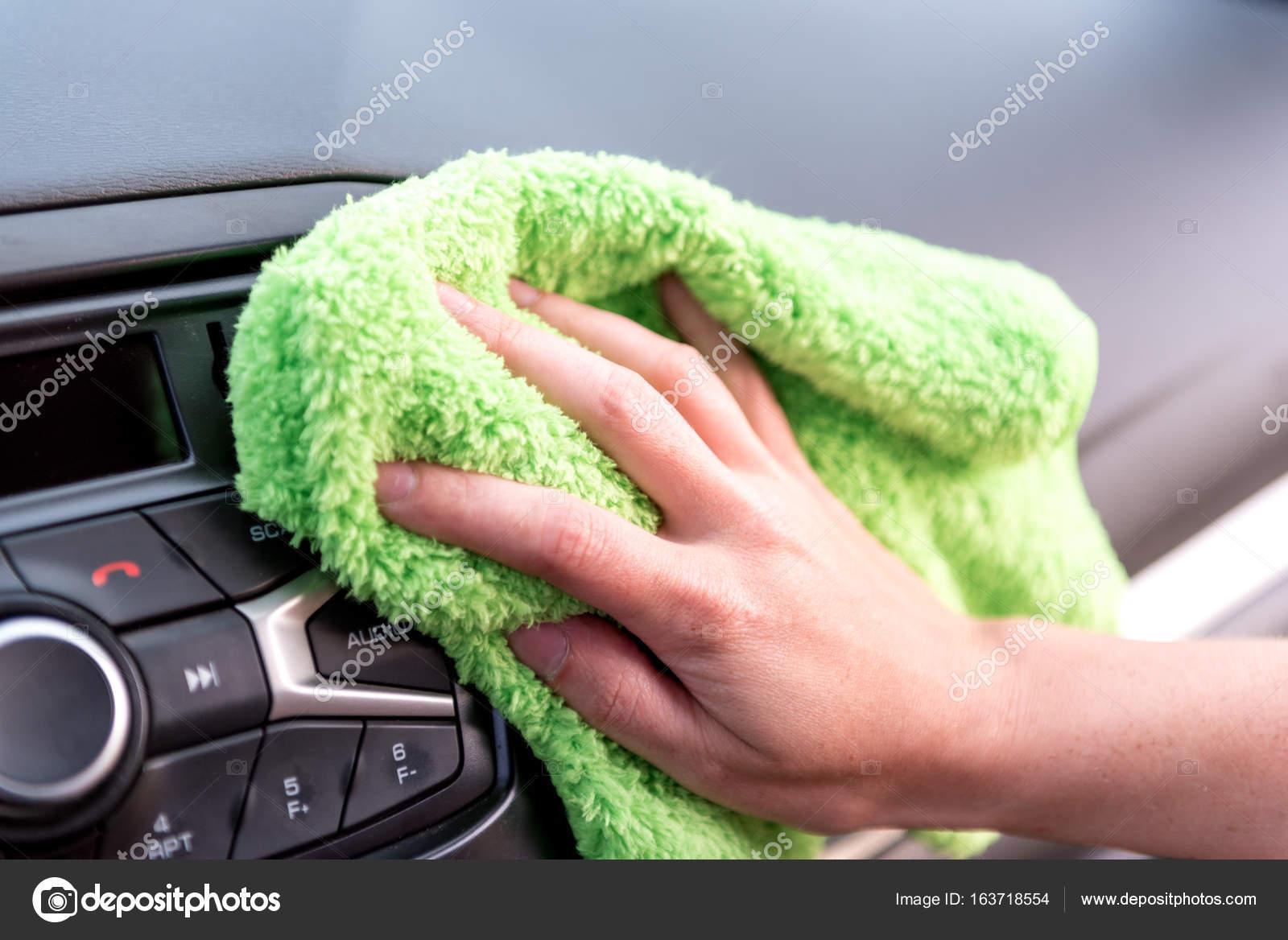 Una mano femenina con un paño de microfibra limpia el panel de un ...