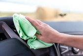 Eine weibliche Hand mit einem Mikrofasertuch reinigt die Plastikverkleidung ein