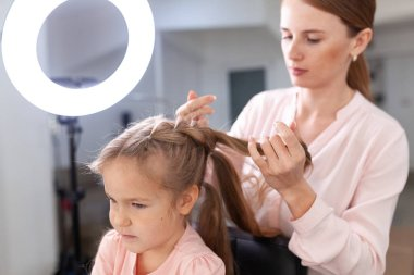 The work of the stylist on hairstyles in a bright salon, the girl makes curls and braids braids of a small beautiful model, indoor