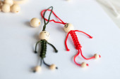 Red and green little men of thread on a white table, macrame