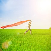 Beautiful young woman jumping on a green meadow with a colored red tissue.