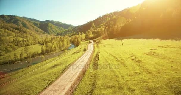 Letecký pohled na rozlišení 4k. Nízký let nad horské venkovské polní cesta a pastviny na ráno. Poblíž zelené stromy, sluneční paprsky a horská řeka