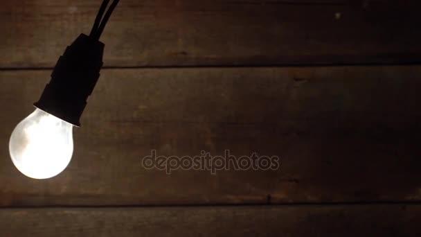 Vintage žárovka houpání na staré dřevěné pozadí