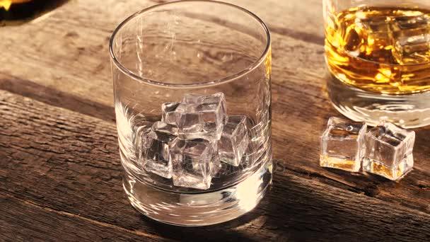 nalil whisky do sklenice s ledem na starý dřevěný stůl