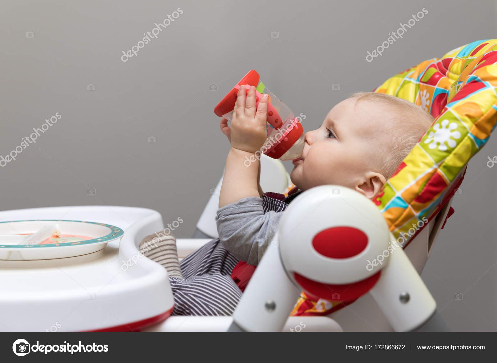 Baby Zitten Stoel.Baby Zitten In De Stoel En Drinkwater Uit Fles Voeding Stockfoto
