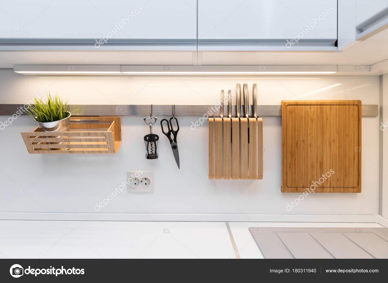 Utensili da cucina appeso sulla guida in cucina bianca lucida